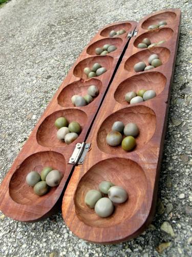 primer plano de un tablero de wari o awalé